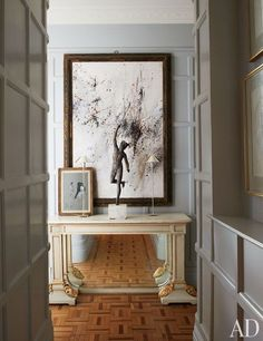 In designers Paolo Moschino and Philip Vergeylen's revamped London flat, a neutral hue brightens up the small foyer, which brings together a small watercolor by Christian Bérard, a garden statue of Mercury, and an 18th-century Swedish console | archdigest.com