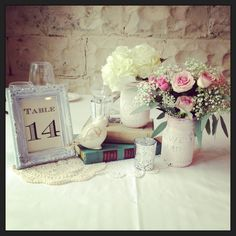 Vintage wedding centrepieces with mason jars and vintage books.  Styled by www.mashedevents.com