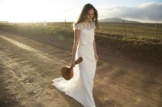 Brud med guitar i hånden i brudekjole med blonde øverst og knapper ned foran