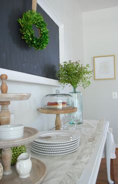 Add popular 'farmhouse' decor to your dining room with a few simple touches. A ruffled linen runner, a large chalkboard, and some tiered stands from @homegoods make for the perfect simple serving station. Add a boxwood wreath and clip some greenery for a pop of nature --and color! Sponsored Pin.