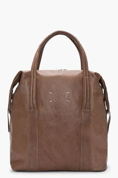 "MAISON MARTIN MARGIELA - Brown waxed camel leather tall tote Structured textured leather tote in brown. Silver-tone hardware. Two-way zip closure at main compartment. Leather carry handles. Removable adjustable shoulder strap with press-stud fixtures at base. Welt pocket at exterior face. Patch pockets and zippered welt pocket at interior. Fully lined. Tonal stitching. Approx. 14"" length, 5"" width, 15"" height. Shell: 100% waxed camel leather. Lining: 100% cotton. Made in Italy. $1350 CAD"