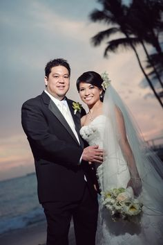 The peachy-pink toned sky creates an amazing backdrop for this portrait of the bride and groom on Waikiki Beach in Hawaii.  Weddings by Grace & Mona.  Photo by Perfekt Photo.