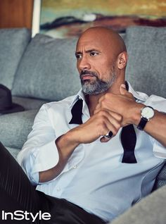 Dwayne Johnson in an Ermenegildo Zegna shirt and Louis Vuitton pants with a Ralph Lauren bow tie, a David Yurman ring, a Montblanc watch, and a Brixton hat (on sofa). InStyle December 2017.
