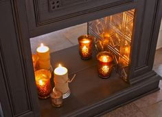 love the idea of covering the inside of a faux fireplace with patterned tins, to reflect candle light