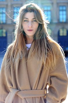 A stunning lady bundled up in a camel coat.
