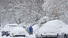 A man walks beside snow-covered vehicles on Pilot House Drive as heavy snow falls in Newport News on Thursday morning. (Photo by Kaitlin McKeown / Daily Press)