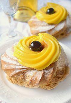 ZEPPOLE NAPOLETANE********** al forno 125 g di farina 190 g di acqua 50 g di burro 3 uova 1 pizzico di sale olio per friggere Per la crema pasticcera 500 ml di latte 150 g di zucchero 4 rossi d'uovo 70 g di maizena 1g di vaniglia 1/2 scorza di arancia Per la finitura