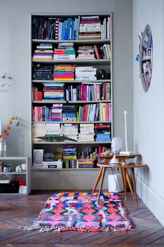 make your bookcase more exciting with colorful books and a coordinating rug #color #livingroom