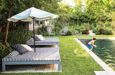 """Another pool where the grass goes right up to the edge - no """"deck"""" needed. The pool beds and umbrella were custom-made, and the metal chairs are vintage, in this beautiful New Orleans backyard oasis."""