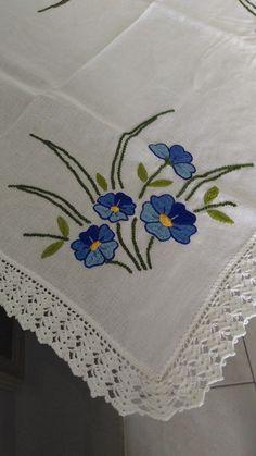 Toalha de mesa quadrada feita no cânhamo fino branco  Técnica: Falso Matiz  Desenho: Flores Azuis  Acabamento: Bico em crochê branco    Medidas:  Comprimento: 78 cm  Largura: 74 cm