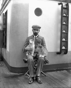 A black and white photo taken in 1905 of a man sitting on a stool onthe deck of a ship with two puppies on his lap.