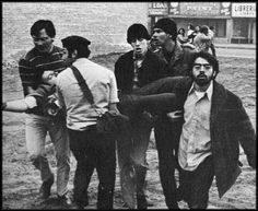 After a confrontation between the National Chicano Moratorium Committee and police during a rally to protest the Vietnam War, Richard Soto (facing away from the camera), a 20-year-old Brown Beret medic, helps carry the injured to safety, 1970. Photo credit: Does anyone know who the photographer is? — at East LA, Los Angeles, California.