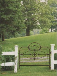 Old iron headboard repurposed into a sweet garden gate