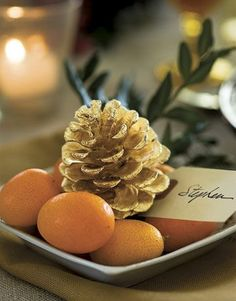 Dress your holiday table and establish your seating plan with place cards attached to gilded pinecones. Here, this take-home gift for guests is nestled among kumquats and a sprig of boxwood set in a shallow dish.