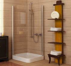Simple walk in closet with white towels beside transparent shower room with big light brown rectangle ceramic wall and floor tiles
