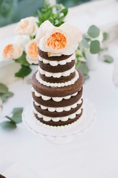 Brown and white layered cake. Peach flowers.