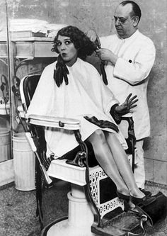 Mary Pickford sitting in a chair in a barber shop in Chicago, Illinois, having her long curls cut off by a barber, c.1928.