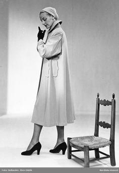 Modell i kappa med dubbla fickor, turban, handskar och pumps, vid en trästol. Fotograf: Sten Didrik Bellander, ca 1953-1957