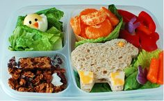 Quick and healthy Easter lunch from  Super Healthy Kids  : Granola with a sesame seed candy in the lower left compartment.  Hard boiled egg chick in the upper left. Main compartment contains sandwich (cut into a lamb)  Carrots, lettuce, red peppers, and red onions (all finger veggies, no fork needed). And a cup of cuties.