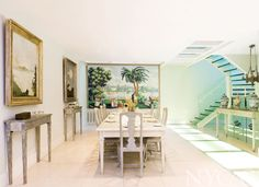 Consoles from the Far East display porcelain and other treasures in the dining room, which features a Rives du Bosphore panel on the wall and Gustavian chairs, all by de Gournay. Glass tiles allow light to filter through the house from upper floors.
