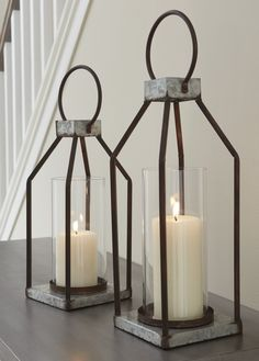Ashley Furniture Diedrick Lantern Set of 2 with Made of galvanized metal with antiqued finish and glass hurricane shade,Indoor/outdoor safe,Pillar candles not included Black Lantern, Lantern Set, Metal Lanterns, Lanterns Decor, Rustic Lanterns, Hanging Lanterns, Farmhouse Furniture, Farmhouse Decor, Modern Farmhouse