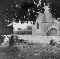 Sainte-Mère-Eglise, June 7, 1944. An American soldier dashes across a church courtyard, in search of a German sniper hidden nearby.