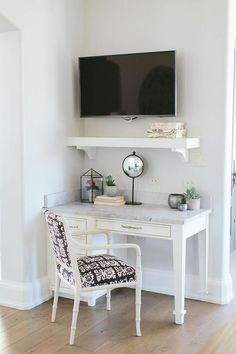 A small corner of the kitchen is filled with a built in desk topped with marble paired with a ikat arm chair placed under a chunky shelf with corbels and a flat panel tv.