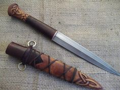 """Witch Dagger by Jeff Helmes, Master Bladesmith. This dagger has a 650 layer Damascus blade. The handle and sheath are made from leather and cherry wood. It has been carved in a """"Celtic"""" motif."""
