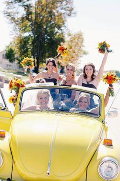 bride and bridesmaids in yellow Volkswagen beetle.