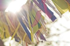 Almost like prayer flags, these fabric ribbons decorated their #outdoorwedding. Photo by Jen Stewart Photography
