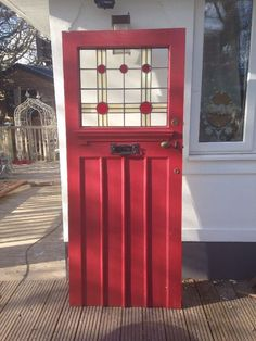 1930s front door in a very true shade of red. The stained glass pattern evokes art deco design.