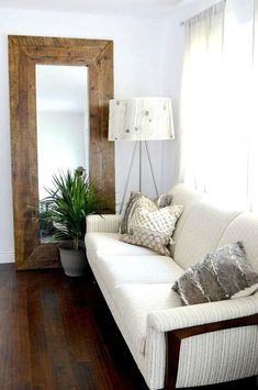 tall wooden frame mirror leaning on wall in small living room with dark floors