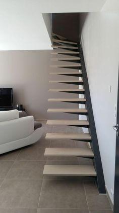 escalier moderne sans garde corps, marches suspendues, en bois clair, avec fixation latérale au mur en métal noir, canapé modulaire et sol carrelage en beige