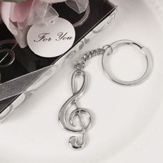 "Thank your guests with the Harmony Treble Clef Key Chain music favors, a token of appreciation that transcends language. This whimsical music party favor celebrates the memorable coming together of friends and family. Sing loudly and proudly with your loved ones on this special day.Measurements: 4 1/4""L Comes in a white gift box with flourish pattern and plastic cover. Gift box is tied with a white organza ribbon bow and adorned with a ""For You"" gift tag"