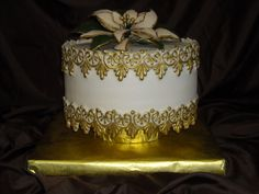 Holiday Cake - Red Velvet with while chocolate mousse filling and amaretto buttercream icing. Fondant border hand painted gold. Fondant poinsettia.