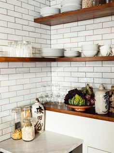 Somehow this insanely small kitchen looks like it offers a lot of storage space, and that is hugely because of the corner shelves, which also make the space ...