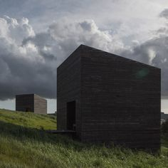 This pair of blackened timber holiday homes by Cheshire Architects stand on the side of a hill that slopes down to the Tasman Sea