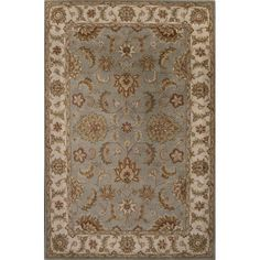 Influenced by rich Oriental rug tradition, this decorative floor covering boasts a graceful floral motif that repeats in its border. Muted blue and ivory hues lend a tranquil touch, and hand-tufted wool treats your feet to sumptuous softness.