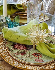 A Wedgewood salad plate depicting birds and flowers reflects the design of the dining room wallpaper. A vintage gold filigree dinner plate sits atop a capiz shell placemat. - Traditional Home ® / Photo: Robert Brantley / Design: Katherine Shenaman