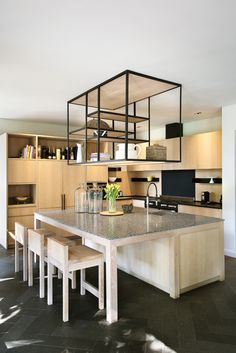 Joe designed the kitchen display bulkhead that is suspended over the working island to store utensils and cook books. Recessed LED lights under the shell light up the surface.