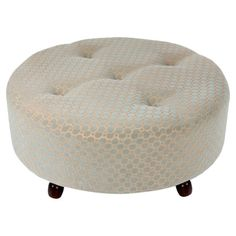 Tufted cocktail ottoman in cream with a wood frame and geometric-print upholstery.  Product: Cocktail ottomanConstruction...