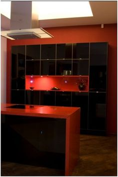 This eye-catching custom made display has black low iron painted glass door fronts. The units have an aluminum frame and black interiors. The red box shelf is in a red high gloss lacquer with four halogen lights. All drawers on the island unit have a soft close mechanism. The worktop is 50mm Eros Stellar red quartz - with sparkly bits! retails for £15000