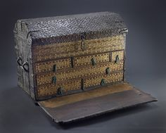 Title:  Wooden travelling chest: 16th century    Description:  Wooden travelling chest,leather covered with brass studs. This chest has a hinged and drop down front to reveal drawers covered in gilded stamped leather.