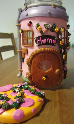 Adorable fairy house made with glass jar and clay.