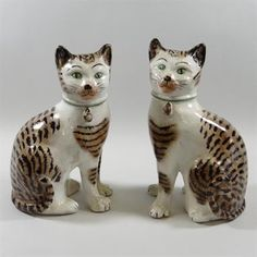 A pair of 19th century Staffordshire pottery models of seated cats