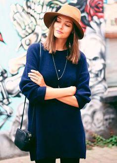 street sttyle look sueter azul, calça preta e chapéu bege.