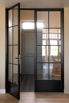 Steel doors with oak flooring and furniture can make a great on-trend hallway - include a pop of grey for a more industrial look!