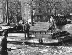 6 maart 1979 - Nu het ijs in de Amsterdamse grachten helemaal weggedooid is, komt al het vuil bovendrijven. De stadsreiniging is dan ook druk in de weer om de grachten schoon te 'vissen'. Deze mensen van de Stadsreiniging zijn bezig in de Erasmusgracht.