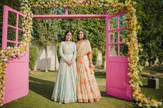 Sister of the Bride - Gursimran & Meher | WedMeGood | Bride in a Blue Lehenga with the Sister in an Ivory and Orange Lehenga with a Door Backdrop as Decor #wedmegood #indianbride #sisterofthebride #sisterofthebrideoutfit #decor #doorbackdrop #purple #floral