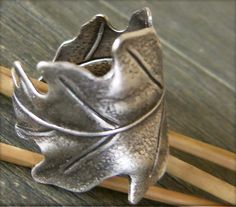 Napkin ring. Salt dough, rolled thin, cut into leaf shapes and scored with veins, curl into a ring, bake as directed, under paint with dark gray and highlight with silver metallic paint.